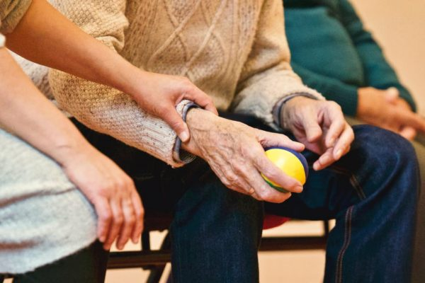 Care taker helping elderly man