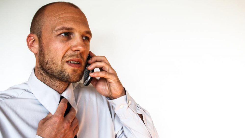 A man looking stressed while talking on the phone