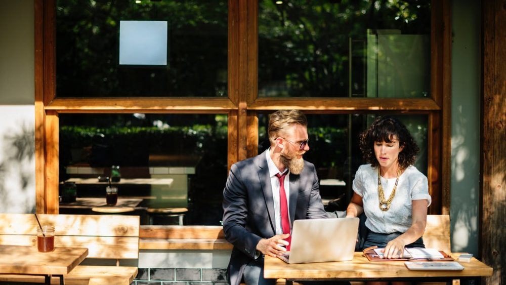 Two employees sitting together talking outside