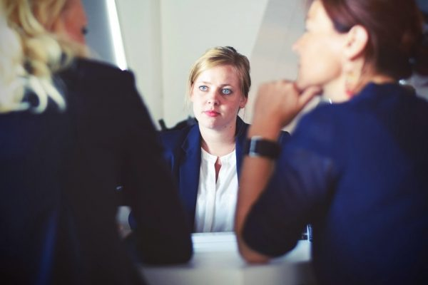 A woman being spoken two by two managers