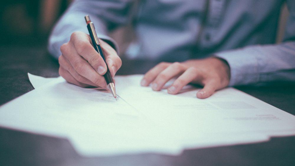 Man sitting at his desk taking notes