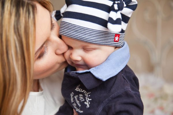 A mom kissing her baby boy