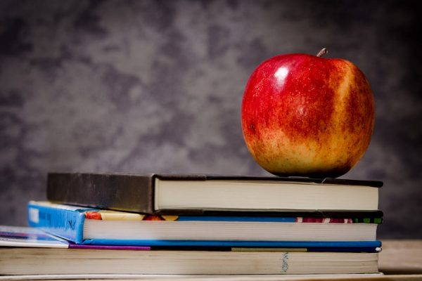 A picture of an apple on some books