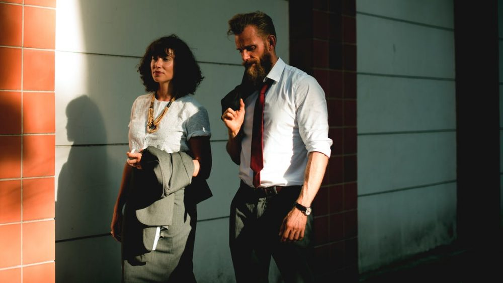 A business man and woman walking together talking