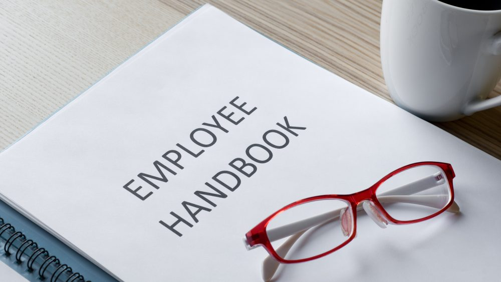 Employee handbook with glasses resting on top