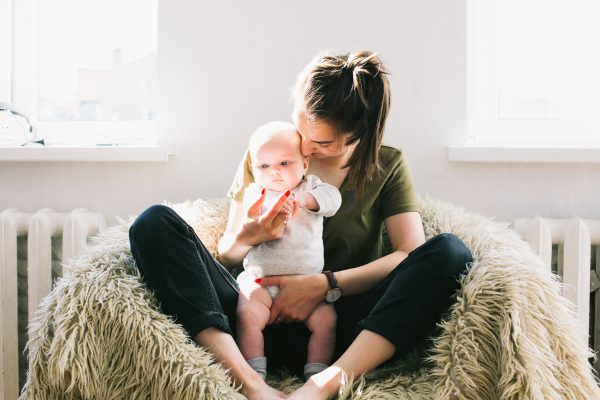 A woman holding her baby at home