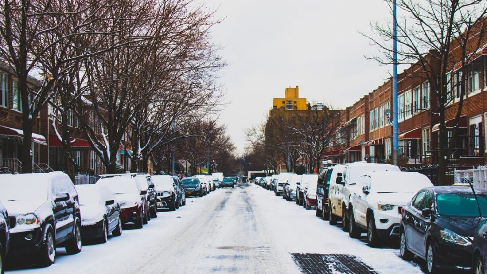 A winter street lined with cars.