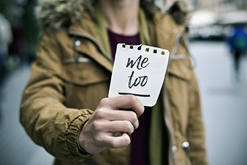 A woman showing a note with the text me too