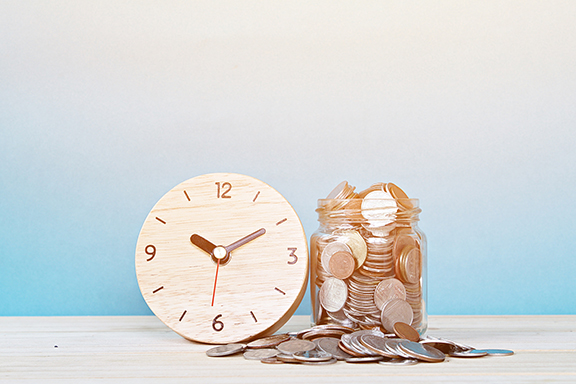 Time clock and coins on white background