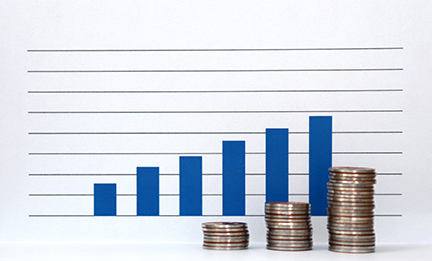 Three pile of coins and a blue bar graph against the white background.