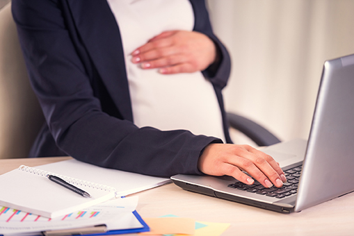 A pregnant woman hand on belly closeup uses laptop in the office