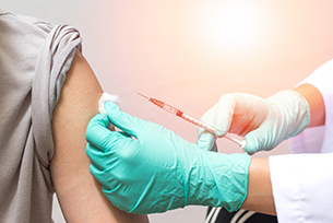 Hands of nurse in medical gloves injecting a shot of vaccine to a man patient