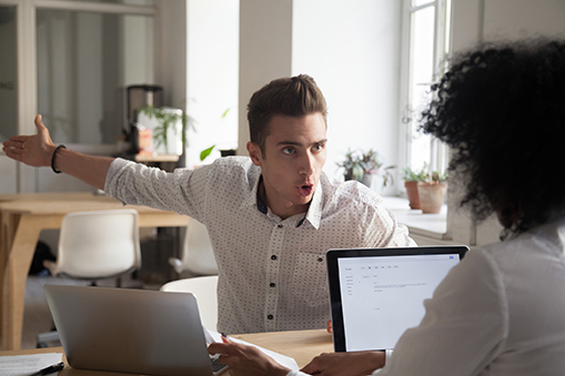 Mad male employee blaming female colleague for mistake