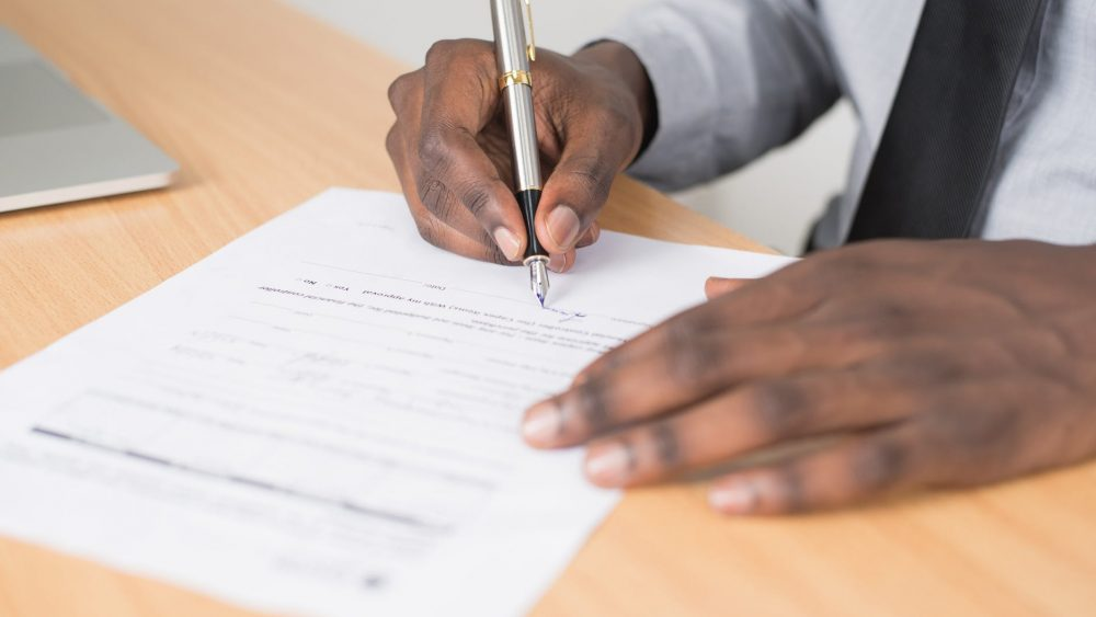 man signing Form I-9 document