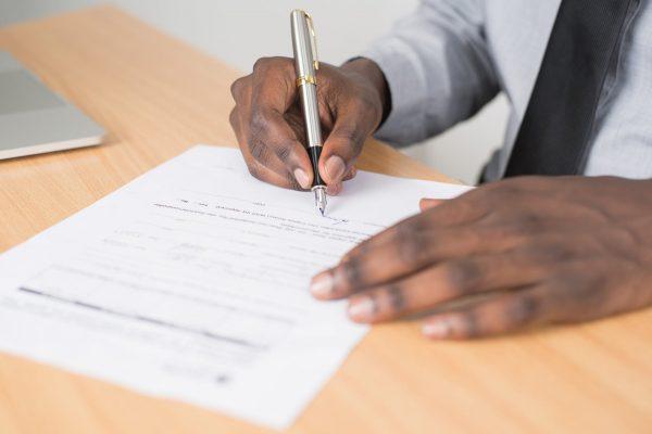 man signing Form I-9 document