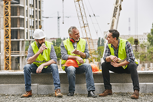 Group of builders in working uniform are eating sandwiches and talking while sitting on stone surface against construction site.