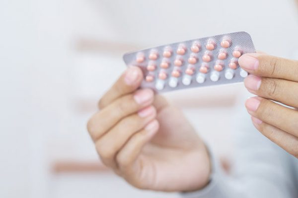 Woman hands opening birth control pills in hand